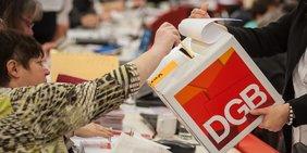 """Wahlzettel wird in Wahlurne mit der Aufschrift """"DGB"""" geworfen"""