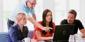 Älterer Mitarbeiter schult jüngere Mitarbeiter an Laptop
