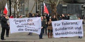 Demonstration auf der Straße mit DGB Fahnen und zwei Transparenten: Gegen die Dummheit, den Hass, die Gewalt und Für Toleranz, Solidarität und Menschlichkeit.