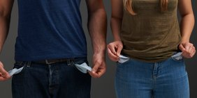 Zwei Personen, die ihre leeren Hosentaschen nach außen stülpen; Symbolbild Armut / Pleite